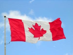 A Canadian flag blows against a blue sky