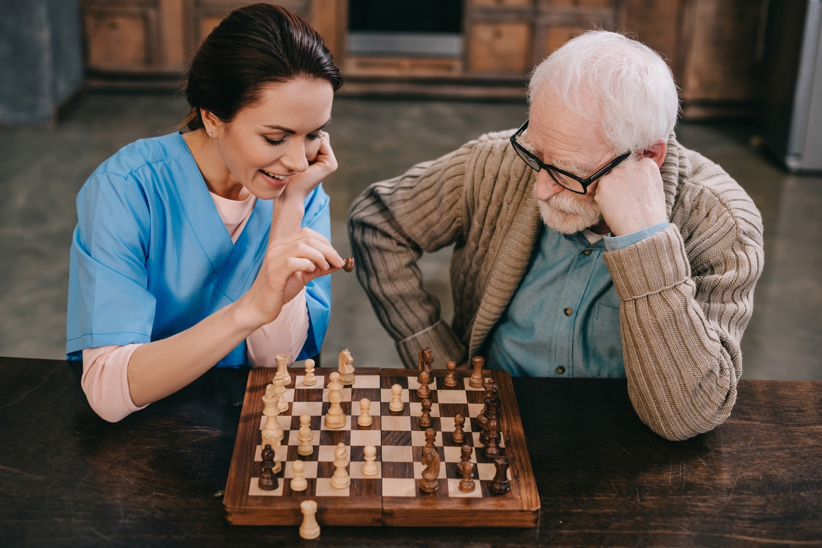 Nurse and elder man playing chess