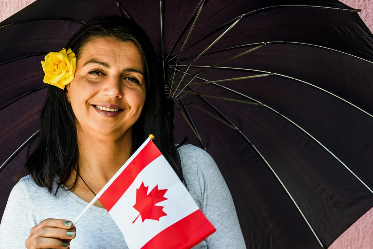 Woman holding small Canadian flag, smiling