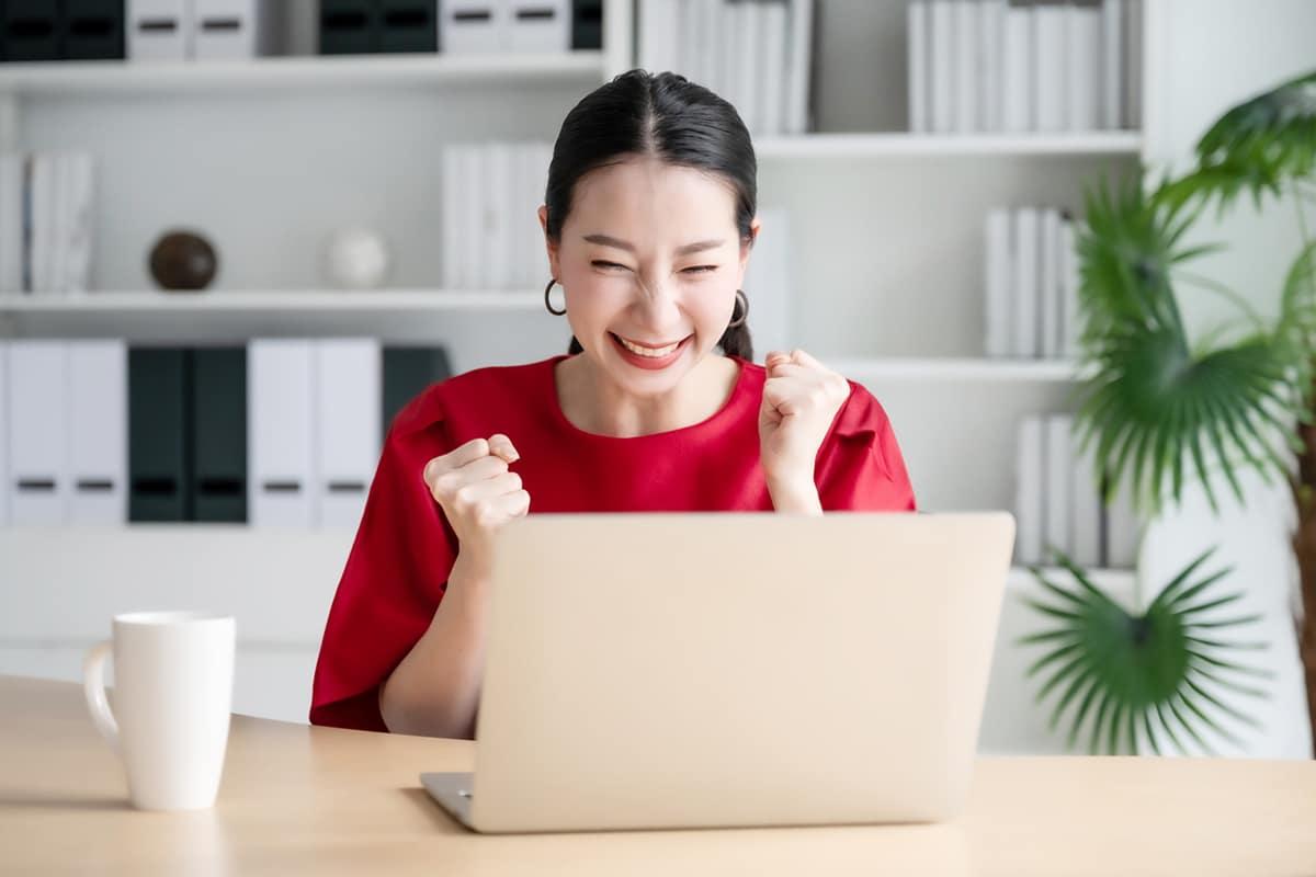 Woman celebrating at computer