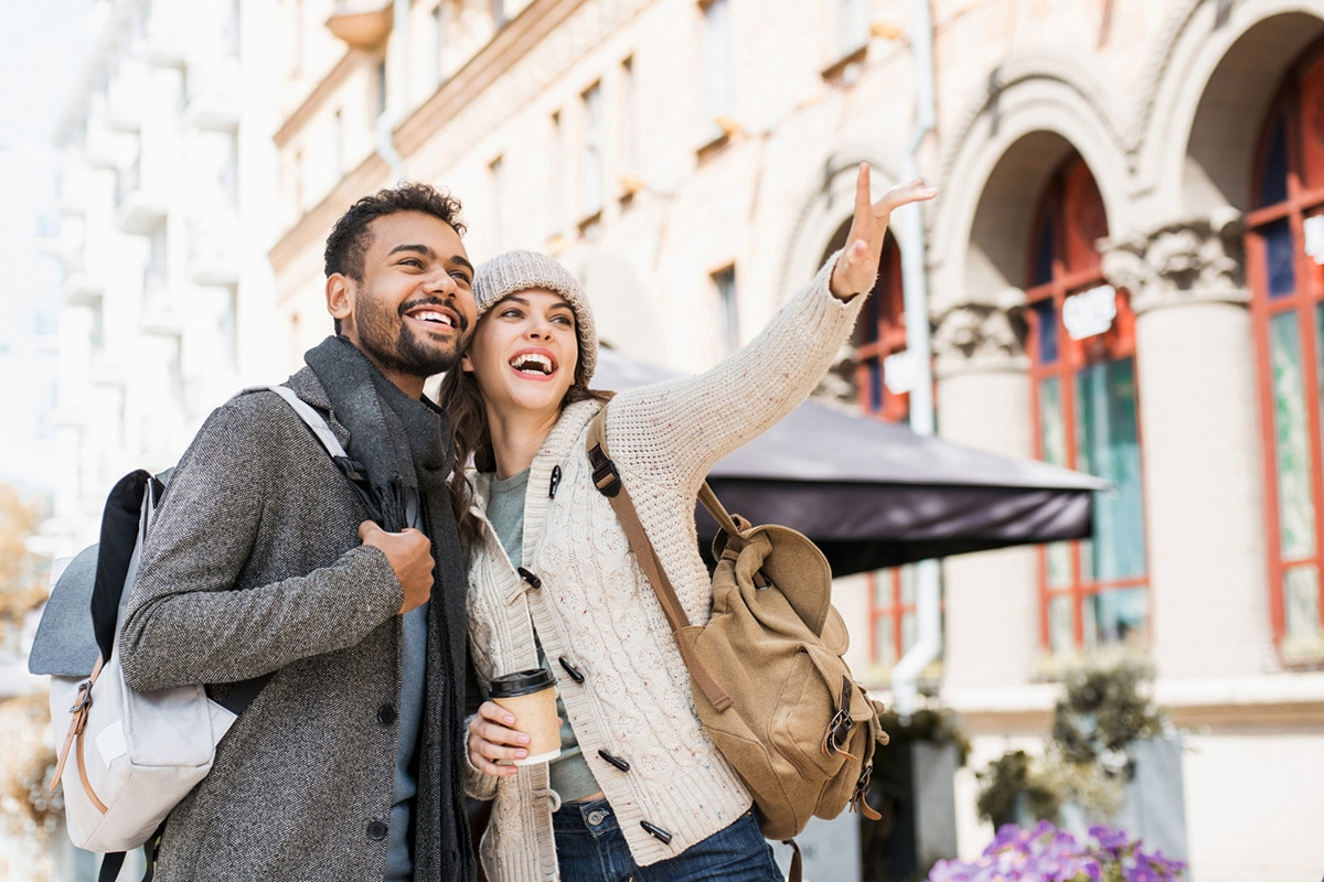 Couple smiling, pointing at colonial architecture
