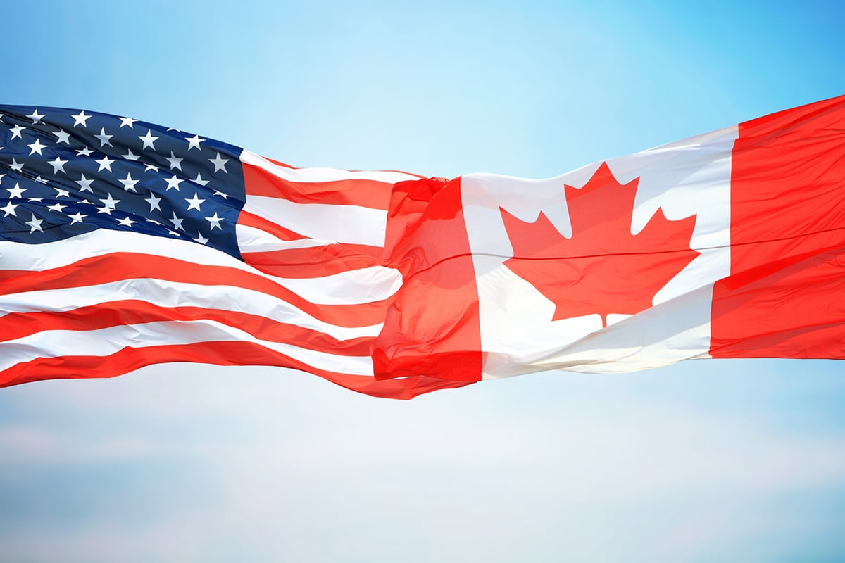 U.S. flag touching Canadian flag
