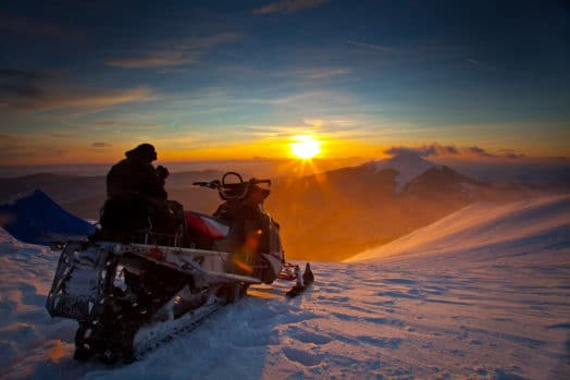 A person sitting on a snowmobile watching the sun set over Canadian mountains
