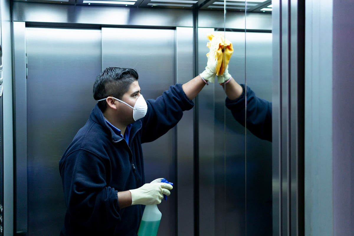 Man cleaning the inside of an elevator
