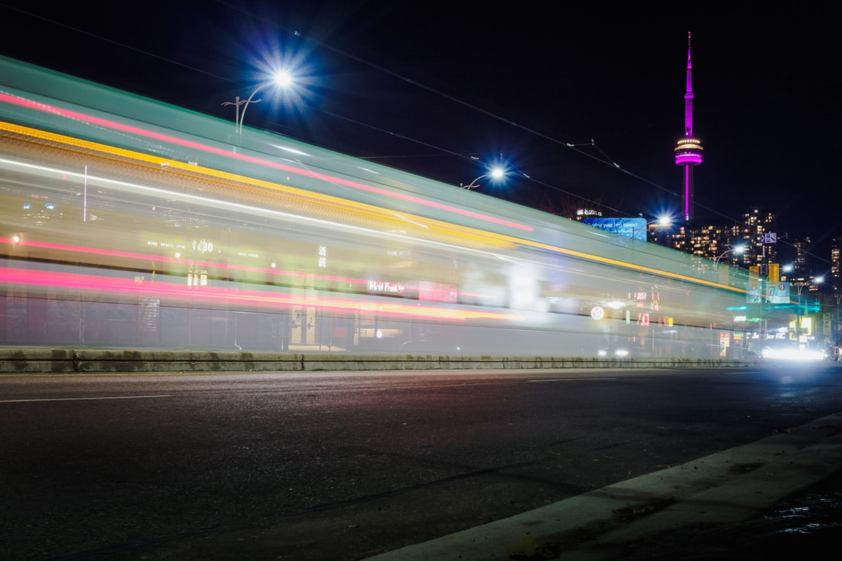 Bus speeding by on Toronto street, CN Tower glowing purple in the background