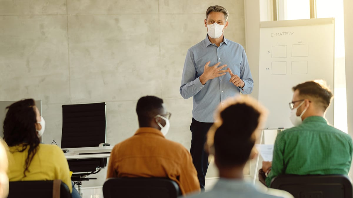 University professor wearing protective face mask while holding a class to group of students during coronavirus pandemic.
