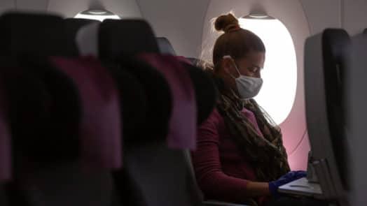 Woman sitting on plane wearing a paper surgeon's mask.