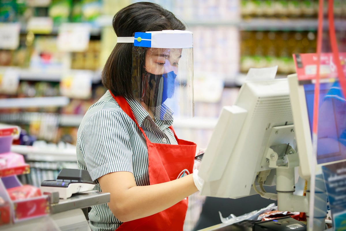 Woman working grocery store wearing covid protective gear