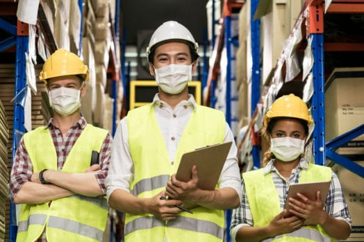 Three workers wearing COVID masks, facing the camera.