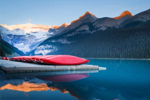 red canoes lined up on Lake Louise dock in Alberta