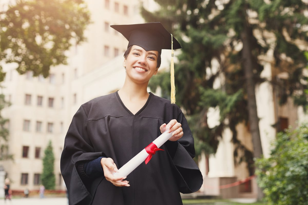 Graduate holding diploma in hand, facing camera