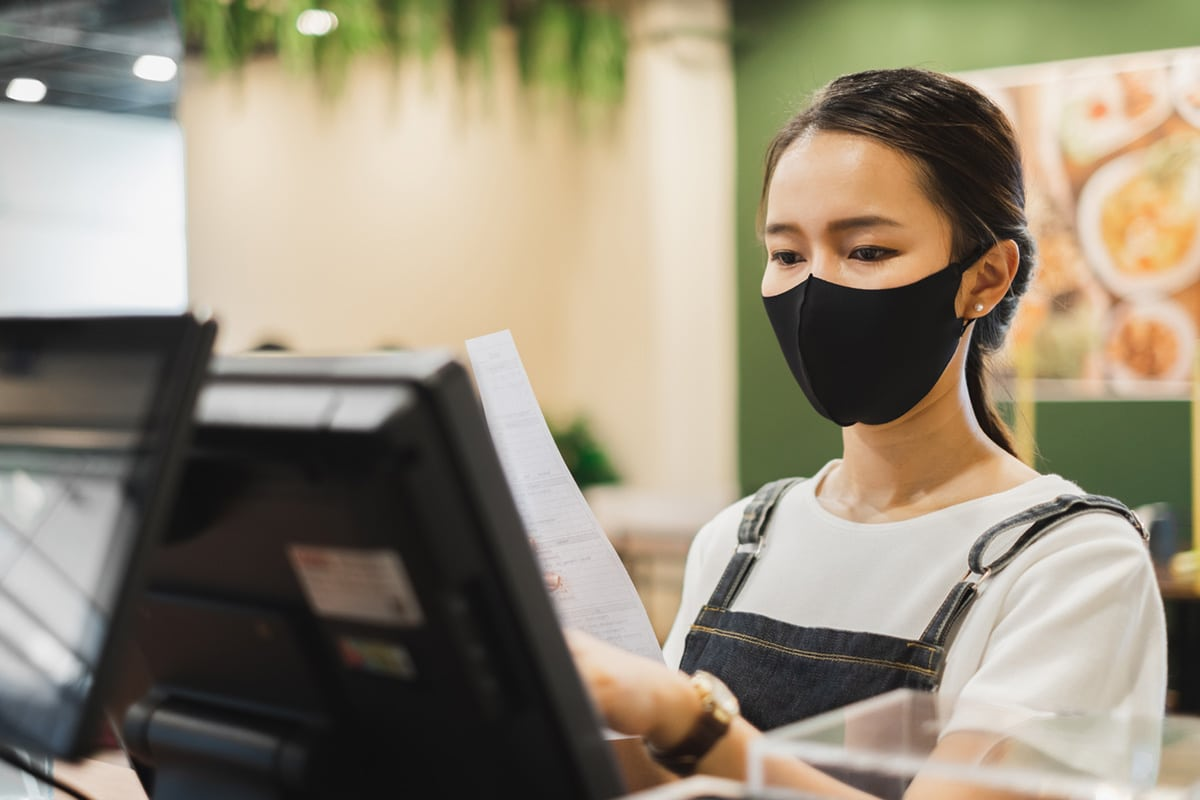 Woman working at a restaurant wearing COVID mask
