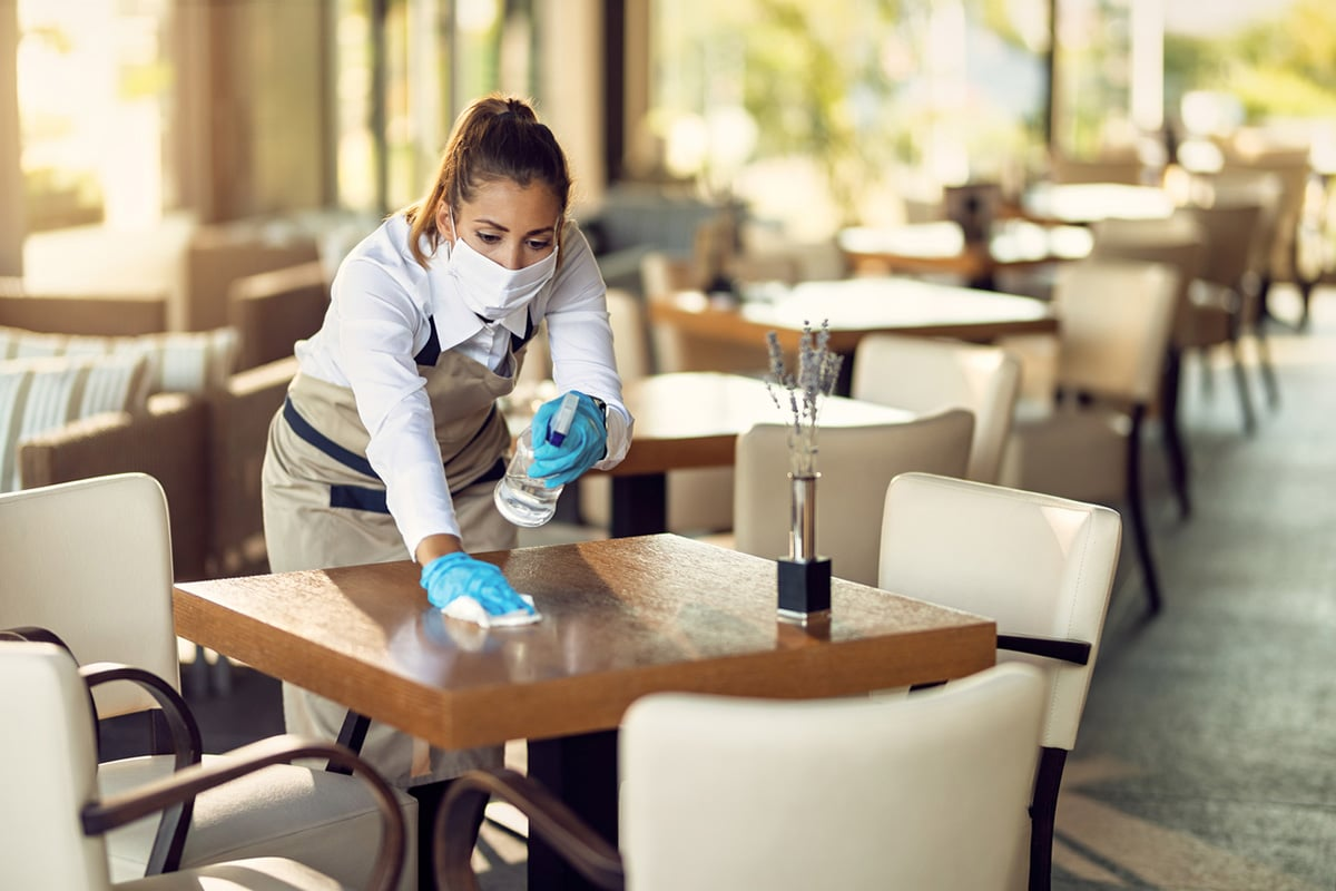 waitress cleaning tables wearing surgical mask