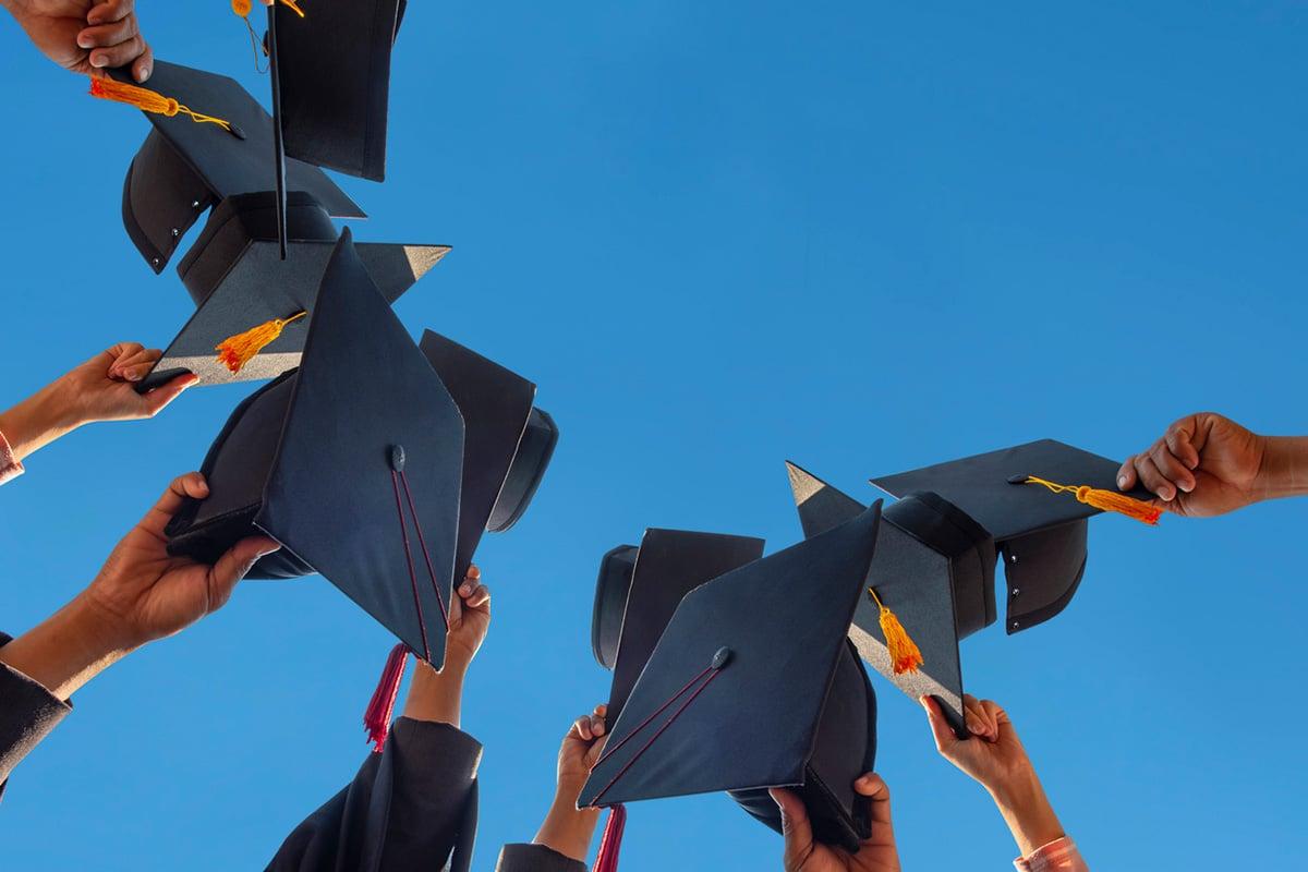 Graduates holding caps up to a blue sky