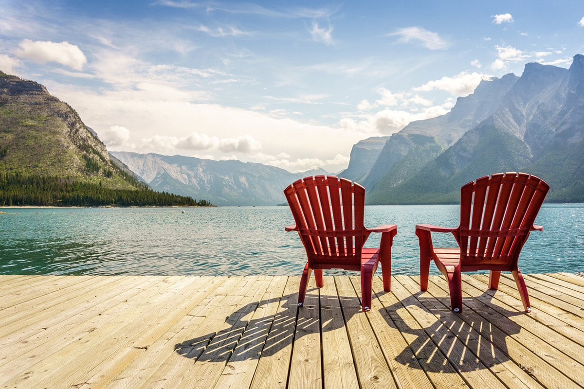 Two empty chairs facing lake and mountains in Banff, Canada