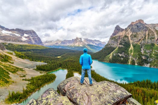 Man in coat overlooking Canadian mountains and lakes