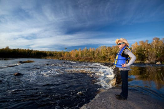 Person standing near waterfalls in Manitoba
