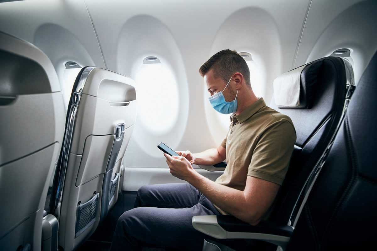 Man checking cellphone on airport, wearing surgical mask