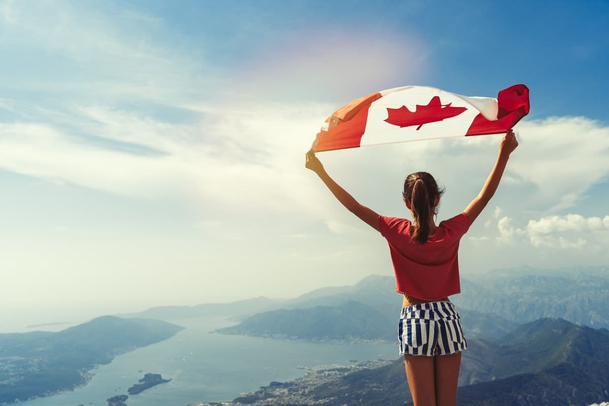 Girl holding Canadian flag on top of mountain